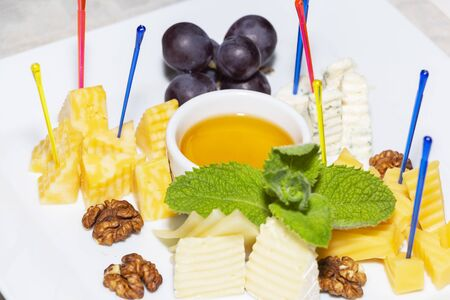 Cheese plate served with grapes, walnuts and honey close-up Imagens