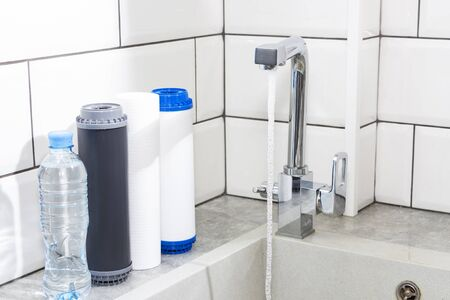 Water filter cartridge in the kitchen. Drinking water filtration system in the kitchen. Clean water at home
