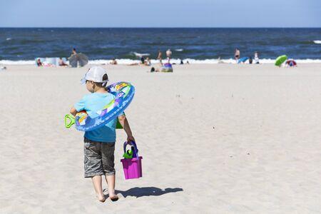 Cute boy with beach toys on tropical beach 스톡 콘텐츠