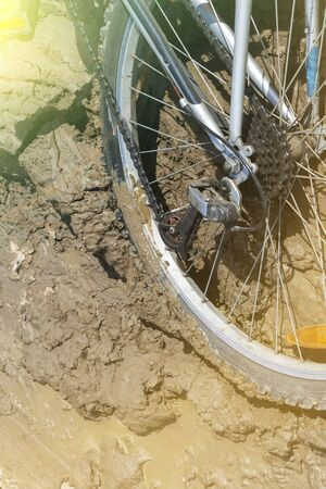 the Bicycle wheel is stuck in the mud. Close up