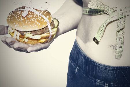 Burger cheeseburger in hands with measure tape isolated on white background. Healthy weight loss diet concept 스톡 콘텐츠