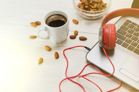 the laptop and red wooden headphones on a light background, a Cup of coffee and scattered almonds. 스톡 콘텐츠