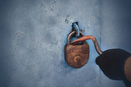 The thief opens the old lock. Safe storage of property