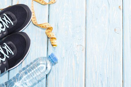 sneakers water bottle on light blue wooden background 스톡 콘텐츠 - 127680084