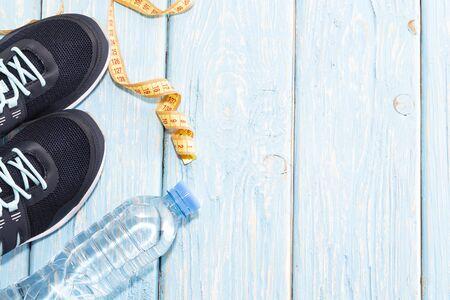 sneakers water bottle on light blue wooden background
