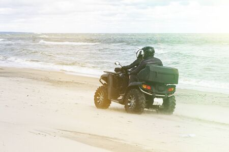 A young guy and a girl in a helmet ride a Quad bike on the beach 스톡 콘텐츠
