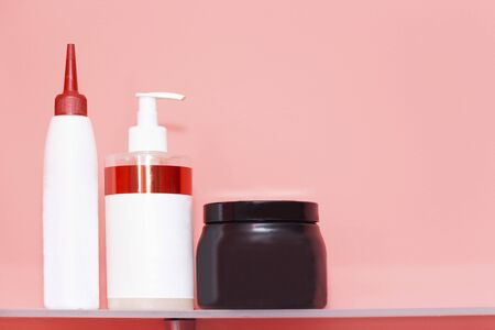 Three bottles of shampoo or shower gel, cream dispenser on colored background with copy space