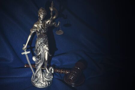 The judges gavel and justice on a dark blue background.