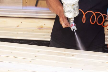 A man covers wooden boards with varnish in the workshop with a spray