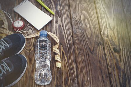 Healthy lifestyle and sports background. Sports shoes, Notepad and pen, and water bottle on wooden background with copyspace, topview.