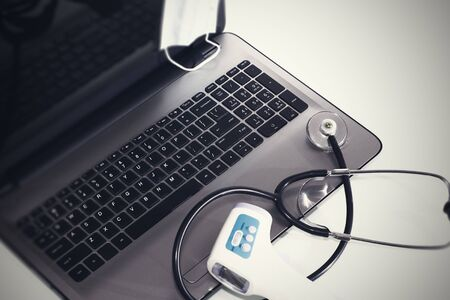 Stethoscope on laptop keyboard. Health care or IT security concept.