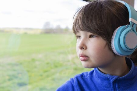 the girl looks out the window of the train and listening to music in headphones