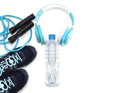 sneakers, water bottle and jump rope, audio headphones on a light white background