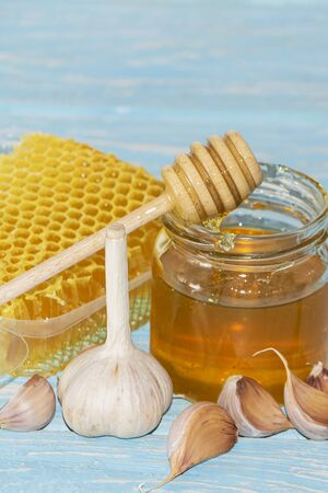 Honey and pieces of garlic on the background of honeycomb. Honey in a glass jar and honeycomb Stockfoto