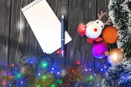 Christmas toys on a wooden gray background, and a Notepad with a pen for writing. Execution of desires