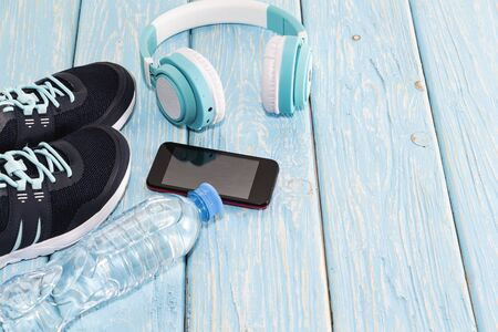 Sports equipment. Sneakers water and headphones, on a light background.