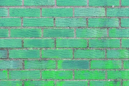 Brick wall painted in bright turquoise color. The texture of the brickwork