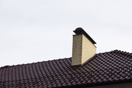 Chimney pipe of brick on the roof of the house