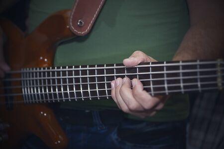 electric bass guitar in male hands, dark background. 写真素材