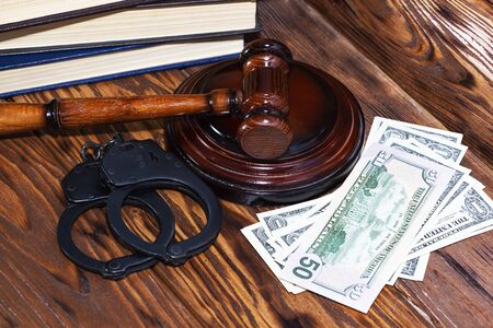 Judges gavel with handcuffs on the background of dollar bills.