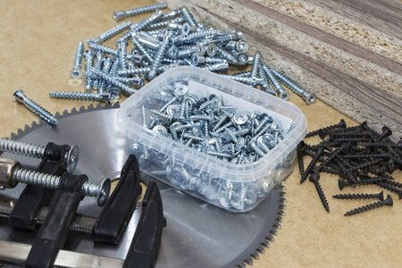 Screws, confirmations for furniture, tape measure, clamp, lie on the table.