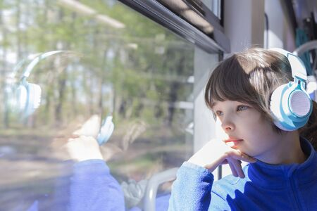 The girl looks out the window of the train and listening to music in headphones.