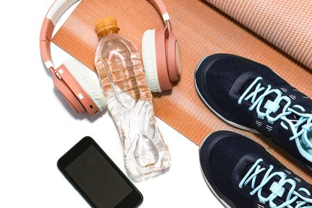Yoga Mat, sports shoes, water bottle concept of healthy living.
