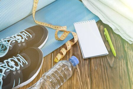 Healthy lifestyle and sports background. Sports shoes, Notepad and pen, stopwatch and water bottle on wooden background. Stockfoto
