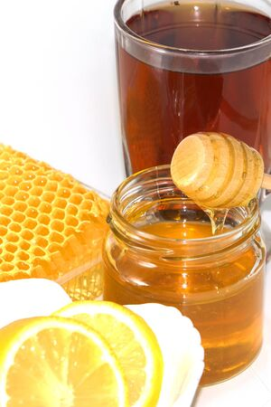 Honey on the background of honeycomb. Honey in a glass jar and honeycomb.
