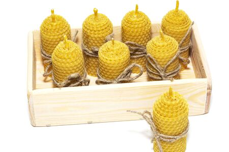 Romantic candles made of natural wax, in a wooden box, made for the holiday. The candle is made of honeycomb