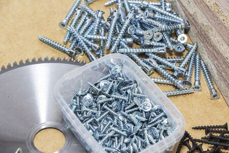 Screws, confirmations for furniture, are on the table. Furniture production.