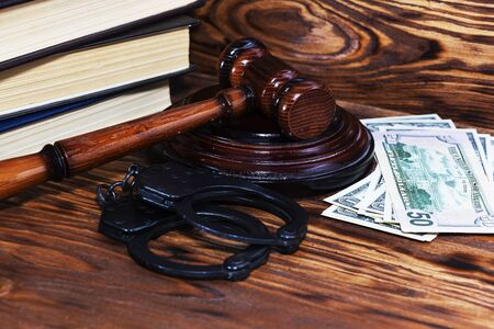 Judges gavel with handcuffs on the background of dollar bills