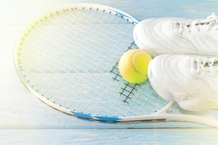 Tennis racket with a ball and sneakers, on a bright background. Photographed in the Studio