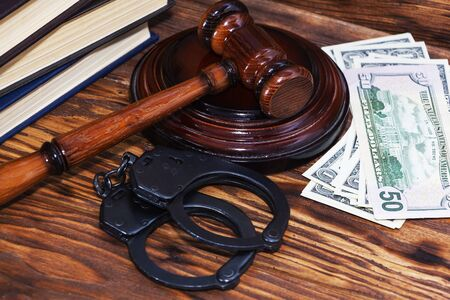 Handcuffs and a wooden gavel in front of manila folders