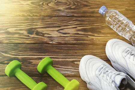 running shoes with dumbbells and a bottle of water on a wooden background. Healthy lifestyle 스톡 콘텐츠