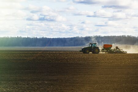 a large tractor with a seeder goes through the field.