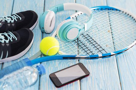 tennis racket. light blue background. sneakers, rocket, ball, water bottle, music headphones.