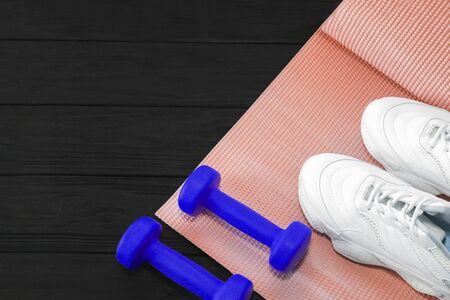 yoga Mat and sports shoes on a black wooden background. Healthy lifestyle, yoga, the concept of sports 스톡 콘텐츠