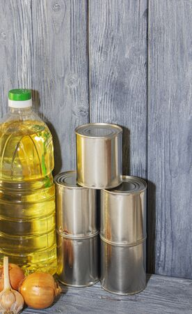 canned food and vegetable oil on a wooden shelf, food crisis. 스톡 콘텐츠