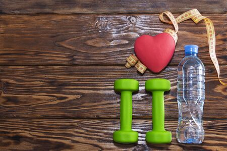 Dumbbells and a red heart on a wooden background. The concept of a healthy lifestyle.