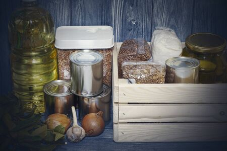 canned food and various cereals on a wooden shelf, food crisis.
