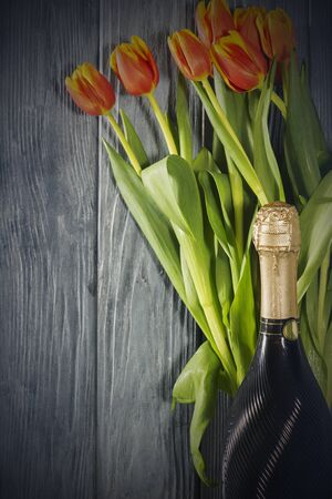 a bottle of champagne and Tulip flowers. the holiday is March 8, mothers Day. Romantic setting. 스톡 콘텐츠