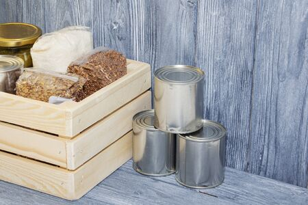 canned food and various cereals on a wooden shelf, food crisis 스톡 콘텐츠