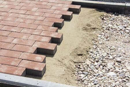 Process of construction of brick paved sidewalk, half built pavement road