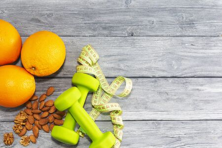 Lots of oranges, dumbbells, measuring tape on a wooden textured background. Fitness, sports nutrition.