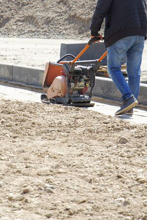 Plate compactor for for soil compaction pavement or sidewalk in the city. Worker is compacting soil by vibratory plate compactor. 스톡 콘텐츠