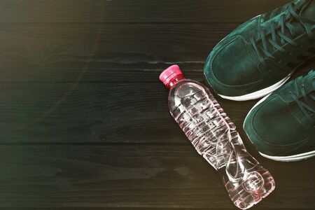 sneakers and a bottle of water on a black wooden background. The concept of a healthy lifestyle. 스톡 콘텐츠