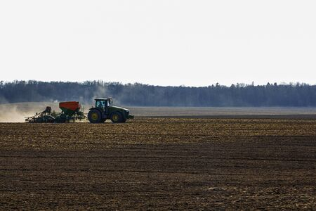 a large tractor with a seeder goes through the field 스톡 콘텐츠