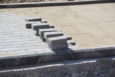 Process of construction of brick paved sidewalk, half built pavement road. 스톡 콘텐츠