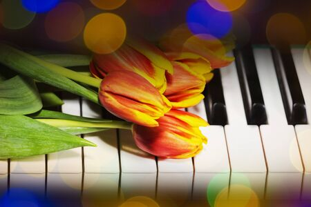Tulips on the piano. The concept of romantic music and melodies
